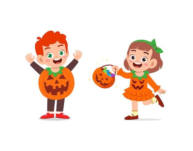 男の子と女の子がハロウィーンのカボチャの衣装を着て祝う