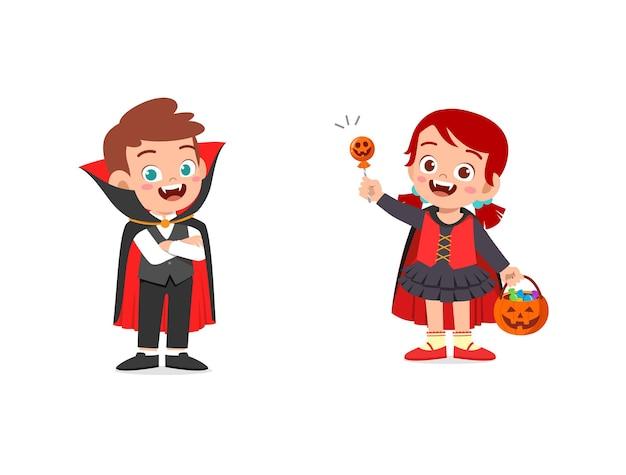男の子と女の子がハロウィーンの吸血鬼の衣装を祝う