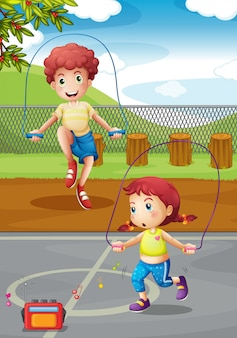 男の子と女の子が公園で縄跳びを行う