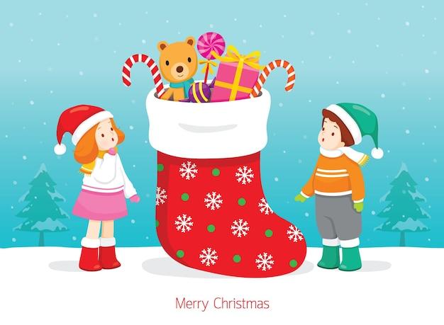 贈り物でいっぱいの大きなクリスマスの靴下でエキサイティングな男の子と女の子