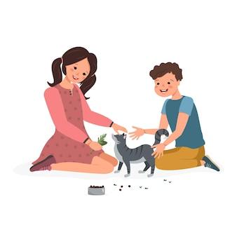 男の子と女の子が猫に葉を与えます子供たちは子猫と遊んで飼い主がペットの世話をします