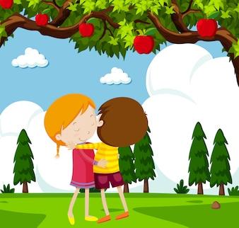 Boy and girl hugging under apple tree