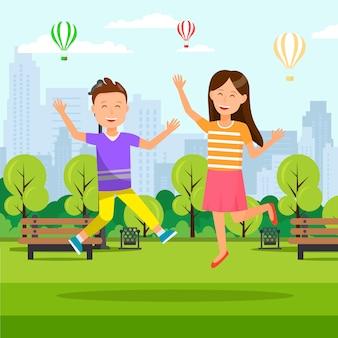 男の子と女の子がシティパークで手を挙げろとジャンプします。