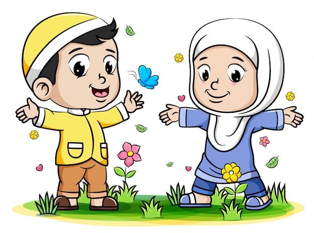 公園で蝶と遊ぶ男の子と女の子のイスラム教徒の子供たち