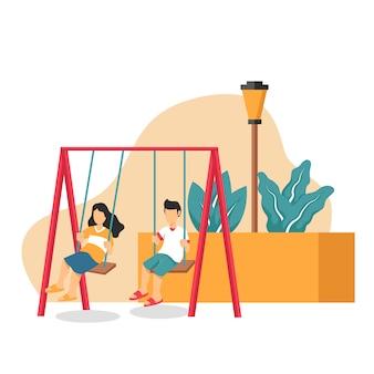 男の子と女の子が公園のブランコで遊んで