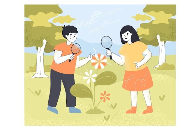 屋外で虫眼鏡を使用して花を見ている男の子と女の子