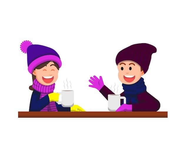 男の子と女の子が冬に温かい飲み物で一緒におしゃべり