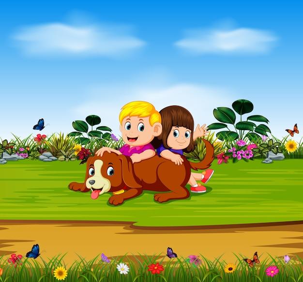 少年と少女は庭で犬と遊んでいる