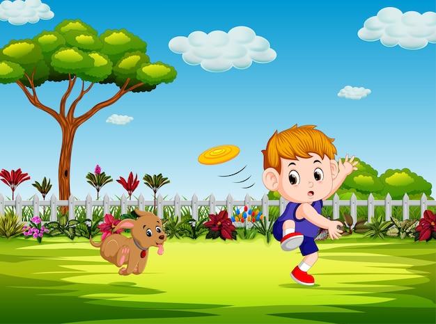 少年は庭の中で彼の犬とフリスビーを演奏している