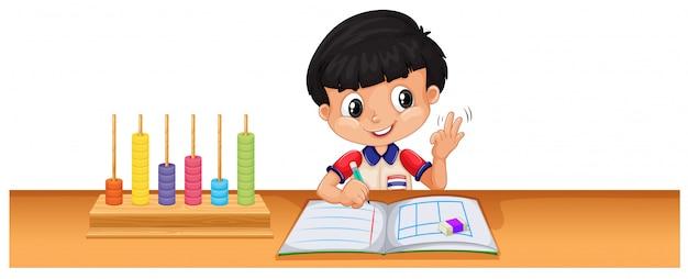 Мальчик рассчитывает математику на столе