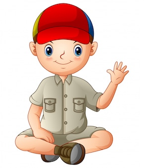 A boy in camping outfit is sitting and waving