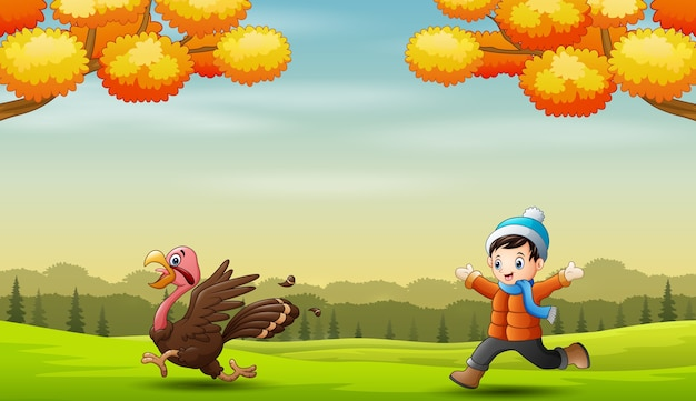 Boy chasing a turkey in the nature landscape