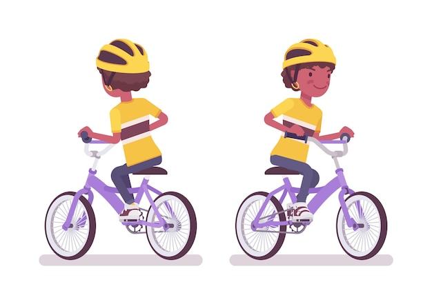 Мальчик ребенок от 7 до 9 лет, черный ребенок школьного возраста, езда на велосипеде