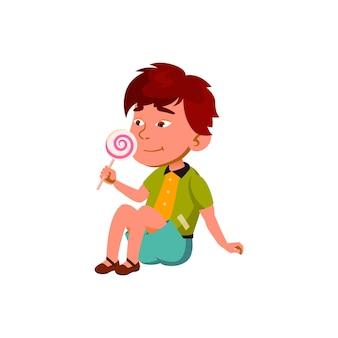 Boy child enjoying sweet lollipop candy vector. asian preteen kid sitting on floor and eating delicious lollipop candy. character tasty dessert, sugary food flat cartoon illustration