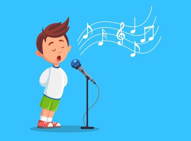 마이크와 함께 노래하는 소년 아이. 노래방 노래