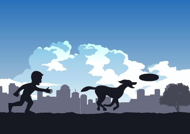 少年は公園で犬と一緒にディスクを遊んで楽しむ