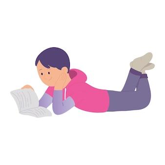 A boy enjoys reading a book while lying down