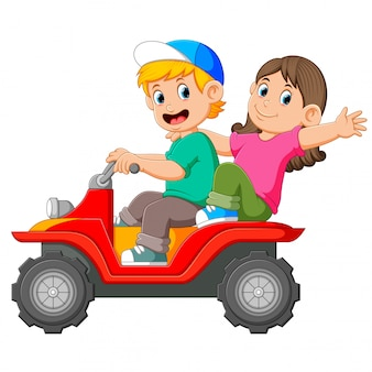 The boy and the girl are riding the atv together