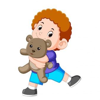 A boy happy play with the grey teddy bear