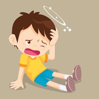 У мальчика головокружение на полу, вокруг его головы кружатся звезды.