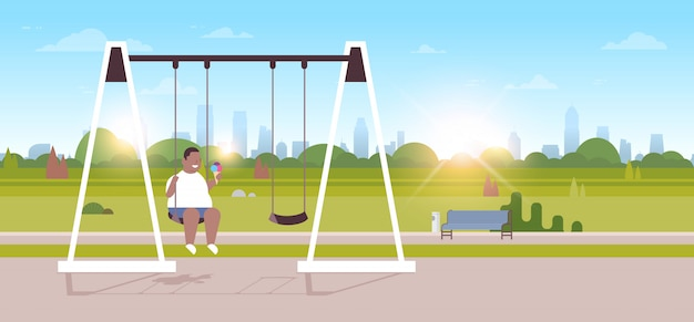 Boy holding ice cream sitting on swing outdoor  overweight guy swinging eating fast food