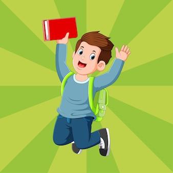 Мальчик держит красную книгу и прыгает со счастливым лицом