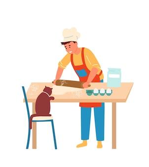 앞치마와 롤링 핀으로 반죽을 만드는 요리사 모자 소년. 계란, 밀가루, 고양이와 주방 테이블.