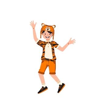 카니발 의상과 호랑이 모자를 쓴 소년. 극장, 새해, 크리스마스 및 휴일을 위한 축제 의류. 아이는 즐거운 얼굴과 행복한 감정으로 춤을 추고 있습니다