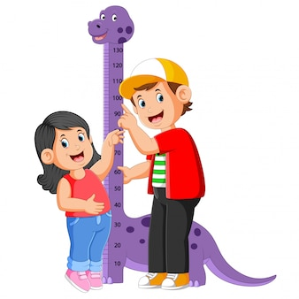 The boy is measuring his sister on the dinosaur measure height