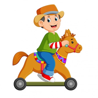 The boy is playing on the horse toy with the wheels