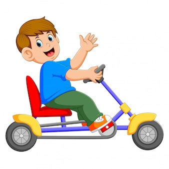 The boy is sitting and riding on the tricycle