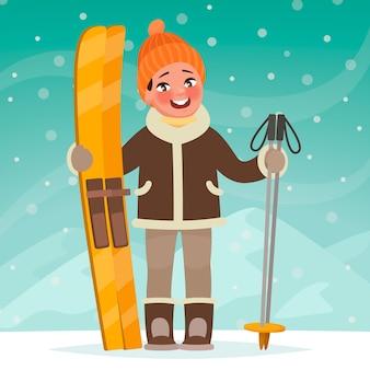 少年は冬の風景を背景にスキーを持って立っています