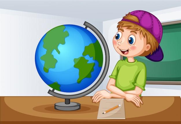 Мальчик смотрит на глобус в классе