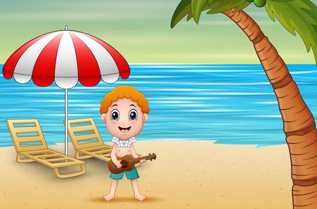 Мальчик играет на гитаре на берегу моря