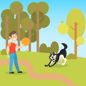 公園で彼のペットの犬と遊ぶ少年