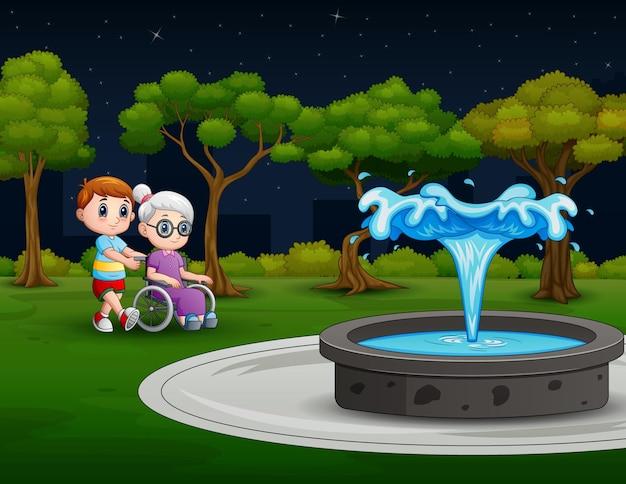 公園のイラストで車椅子で祖母を押す少年