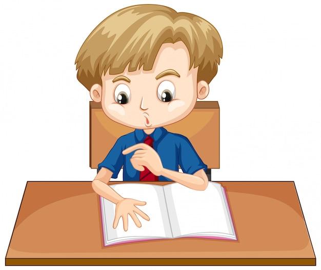 机の上の本を読んでいる少年
