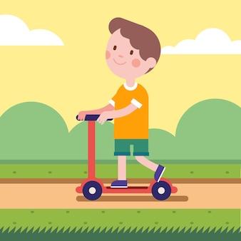 Мальчик едет на скутере на парковой дороге