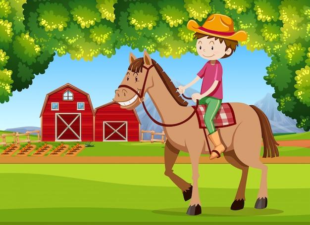 A boy riding horse at farmland