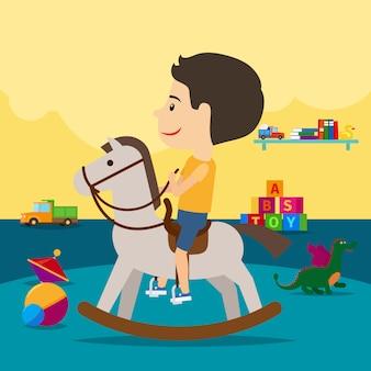 Boy riding toy horse in kindergarten