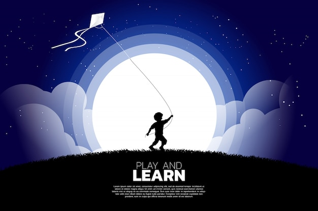 Boy running with flying kite in the sky at night.