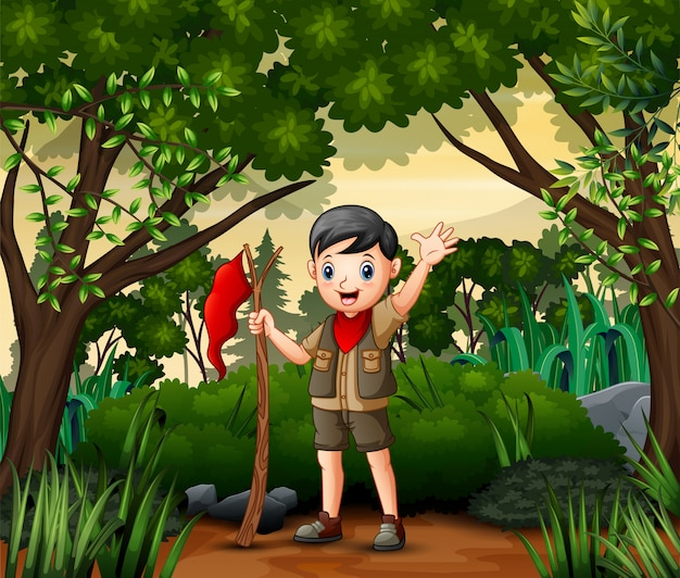 A boy scout holding a flag walking in forest