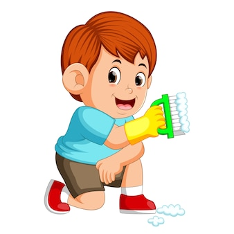 Boy sitting and holding the green brush to clean up the things