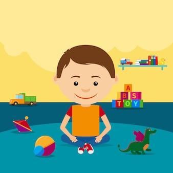 Мальчик сидит на полу с игрушками