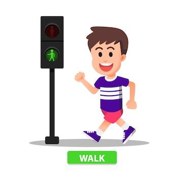 Boy starts walking according to the traffic light indicator