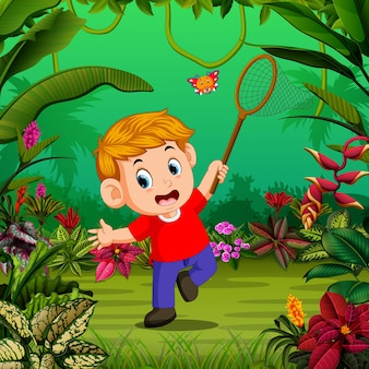 Boy tries to catch a butterfly in the forest