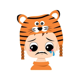 Boy with big eyes and depressive emotion crying tears face in tiger hat cute kid with sad face in a ...
