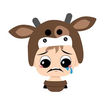 ブロンドの髪と泣いて涙を流している少年は、かわいいcの牛の帽子の頭の中で悲しい顔の憂鬱な目をしています...