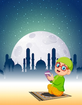 The boy with the glasses are reading al quran in the bright moonlight