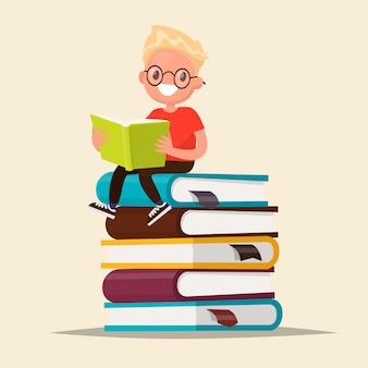 Мальчик в очках, читая книгу, сидя на стопку учебников.